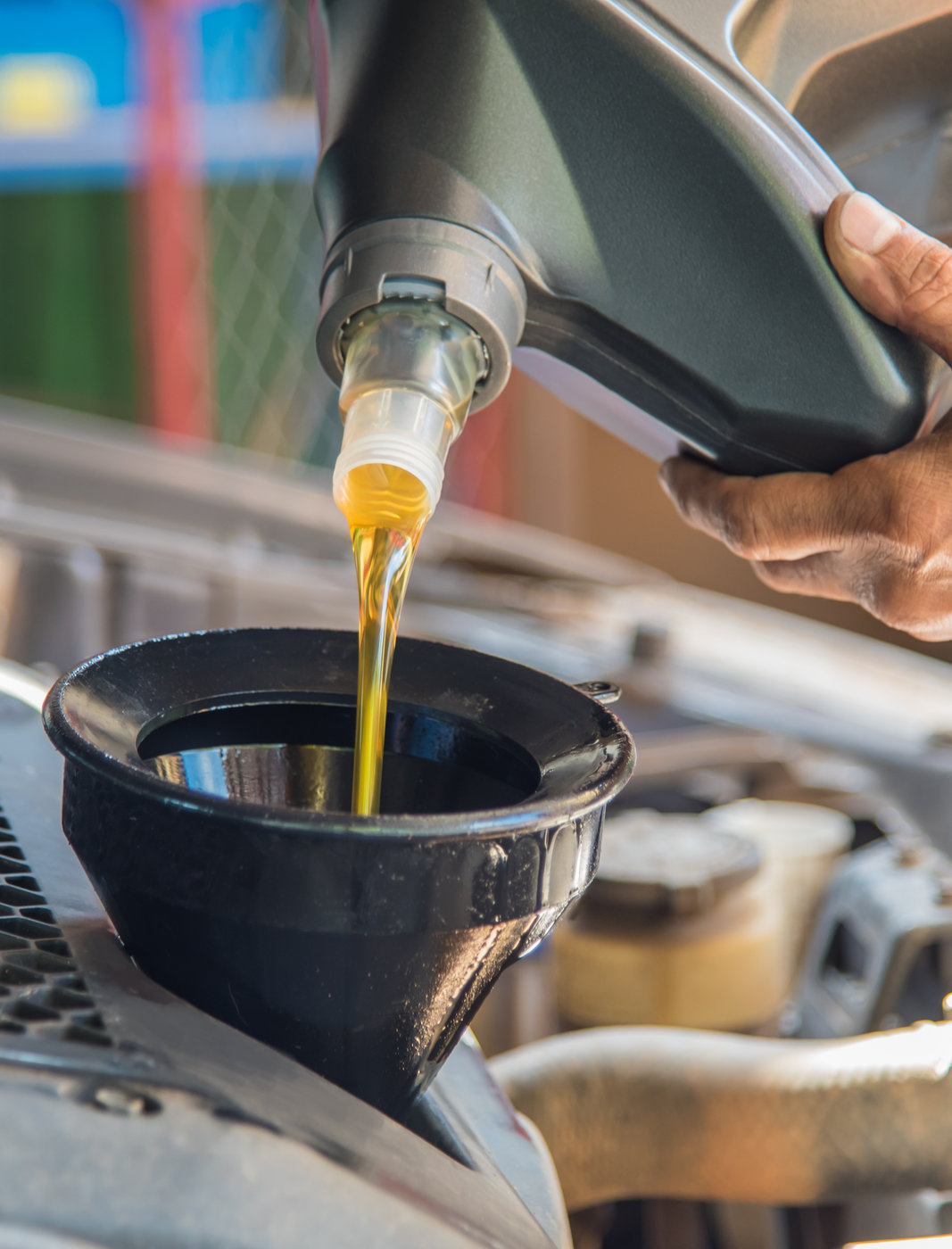 Mechanic filling up a vehicle with engine oil - MOT & Servicing Bristol